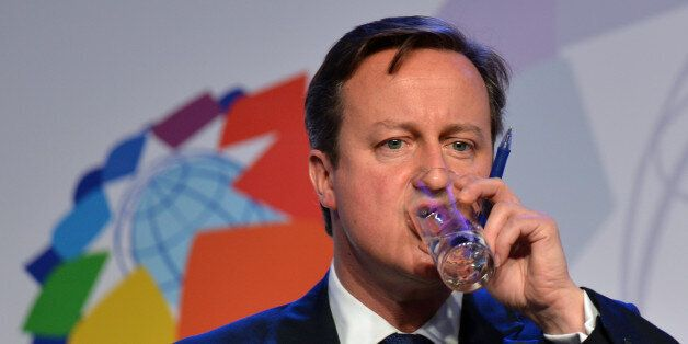 British Prime Minister David Cameron sips water during a press conference held on the second day of the...