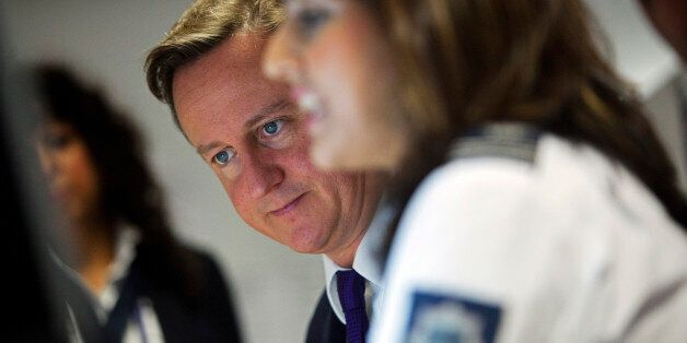 LONDION - OCTOBER 10: Prime Minister David Cameron watches security monitors as he talks to UK border...