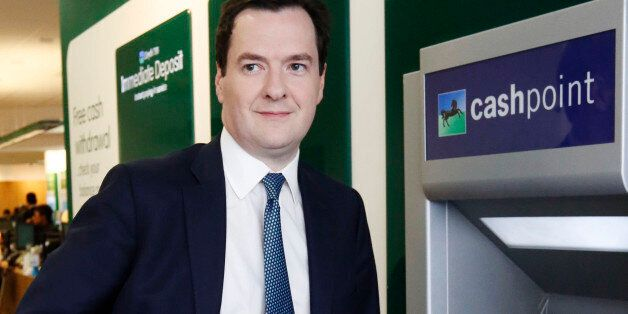 Chancellor of the Exchequer George Osborne uses a Lloyds Cashpoint machine to withdraw some money during...