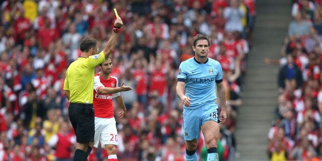 Referee Mark Clattenburg (left) shows the yellow card to Manchester City's Frank Lampard