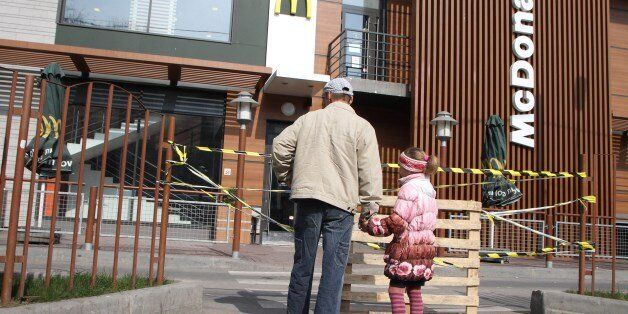 A man and a little girl look at a closed McDonald's in the Crimean capital Simferopol on April 4, 2014....
