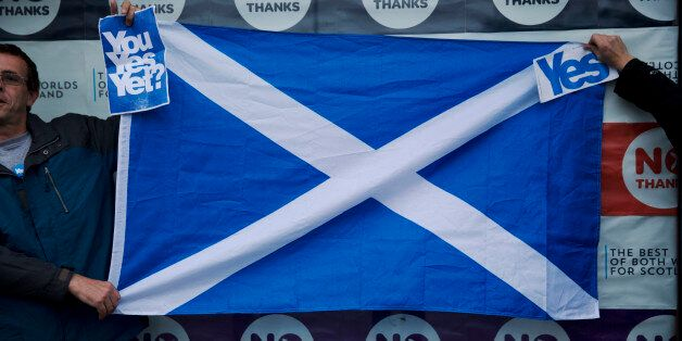 Two Scottish independence referendum Yes supporters hold a Scottish Saltire flag up outside