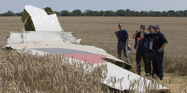 Australian and Dutch investigators examine a piece of the Malaysia Airlines Flight 17 plane, near the...
