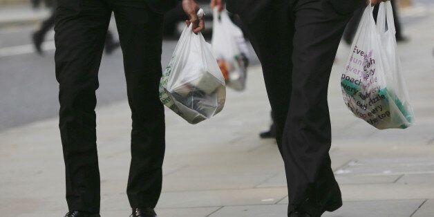 Male customers are seen carrying Tesco branded shopping bags after leaving a Tesco Metro supermarket...