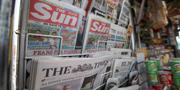 Copies of News Corp.'s newspaper titles, The Sun and The Times, are seen for sale on a newsagent's stand...