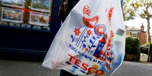 A shopper carries a Tesco supermarket bag in London, Monday, Sept. 22, 2014. Tesco, Britain's largest...