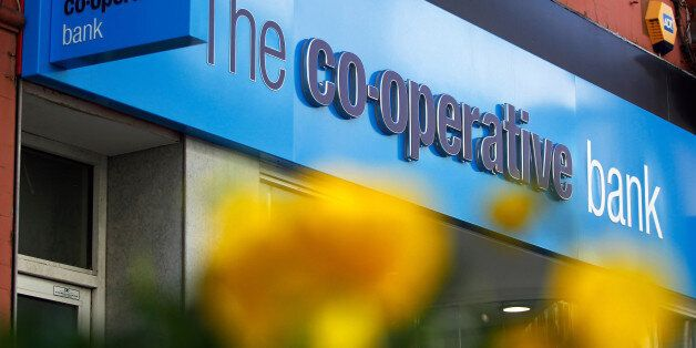 A sign sits above the entrance to a Co-Operative Bank Plc bank branch in Altrincham, U.K., on Tuesday,...