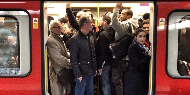 Passengers squeeze on to a busy tube train during strike, at kings cross
