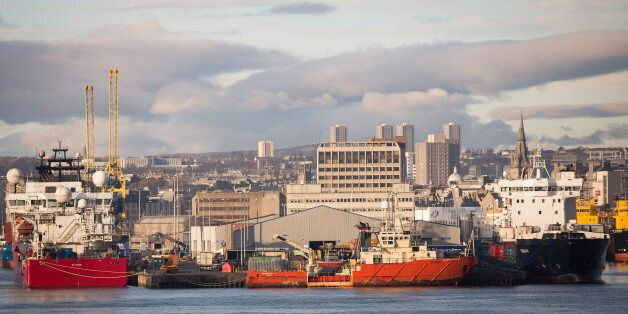 Vessels sit docked at Aberdeen Harbour, operated by the Aberdeen Harbour Board, as the city skyline is...