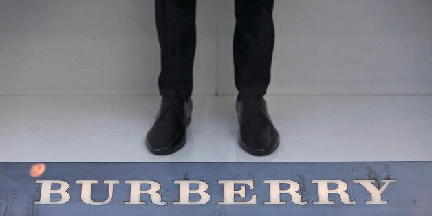 A mannequin stands beyond a logo in the window display of a Burberry Group Plc luxury clothing store...