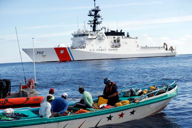 Coast Guard officers board a small fishing boat accused of smuggling cocaine in the Pacific Ocean in...