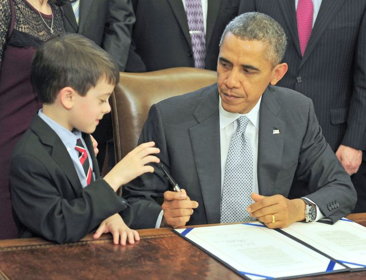 Obama presents a pen to Jacob Miller after signing legislation.