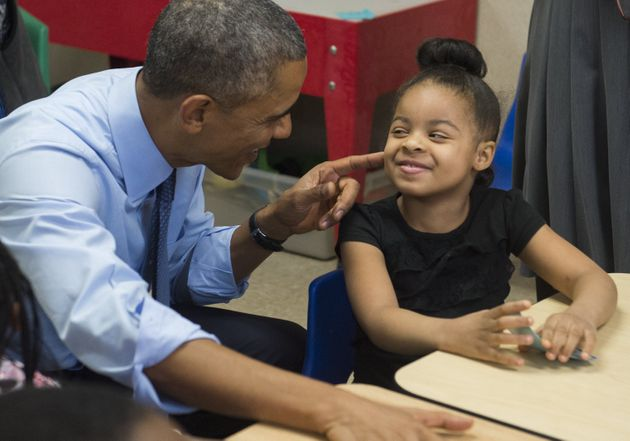 Obama talks with Akira Cooper during a visit to a classroom at the Community Children's Center in Lawrence,...