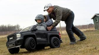 In this Thursday, March 28, 2019 photo, Eladio Beltran, right, pushes his children, Caleb, 4, left, and Jayem, 3, in their car at their home in Albion, N.Y. Beltran faces deportation because he was arrested for driving without a license. In New York and elsewhere, the idea of extending new privileges to those without legal immigration status has been resisted. But a renewed push across the country to allow them to get driver's licenses resonates strongly among those who make their living in the rural crop fields, dairy farms and fruit orchards where the need for everyday transportation can be the greatest.  (AP Photo/Heather Ainsworth)