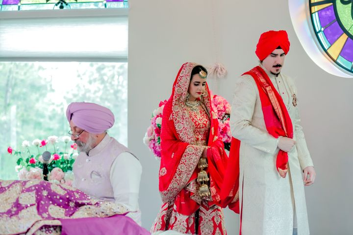 The author and her husband at their Sikh wedding walking around her father and the Guru Granth Sahib.