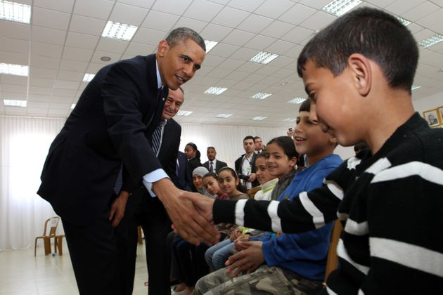 Obama shakes hands with Palestinian children during his visit to Al Bera Youth Center in the West Bank...