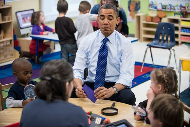 Obama plays a learning game while visiting children at College Heights Early Childhood Learning Center...