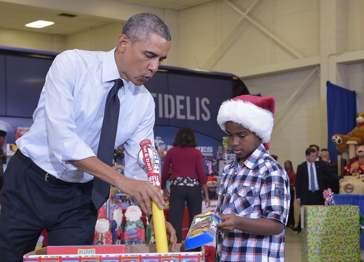 Obama and a young boy sort toys and gifts for the Marine Corps Toys for Tots campaign at Bolling Air Force Base in Washington, D.C., in December 2014.