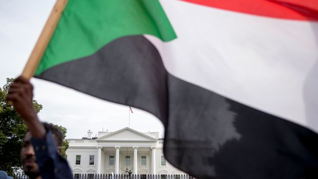 The White House is visible behind a man holding a Sudanese flag as Sudanese Americans rally outside the White House in Washington, Saturday, June 8, 2019, in solidarity with Pro-democracy protests in Sudan. Pro-democracy protest leaders in Sudan on Saturday called on Sudanese to take part in acts of civil disobedience in a bid to pressure the military to hand over power after the deadly break-up of their main sit-in in the capital of Khartoum earlier this week. (AP Photo/Andrew Harnik)