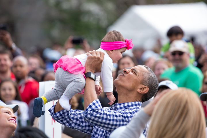 Obama plays with a baby at the 138th Annual Easter Egg Roll at the White House in March 2016.