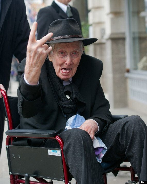 Ronnie Biggs Sticks Up Fingers At Photographers Outside Bruce Reynolds' Funeral