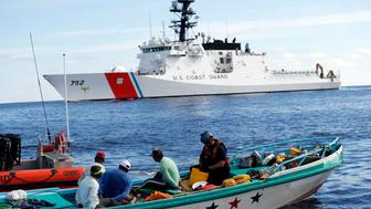FILE - In this Feb. 23, 2017 file photo, a U.S. Coast Guard law enforcement team from the USCG cutter Stratton boards a small fishing boat that was stopped carrying close to 700 kilos of pure cocaine, in the Pacific Ocean hundreds of miles south of the Guatemala-El Salvador border. The U.S. Coast Guard is teaming up with the Mexican and Colombian navies off South America's Pacific coast to go after seafaring smugglers, opening a new front in the drug war. (AP Photo/Dario Lopez-Mills, File)