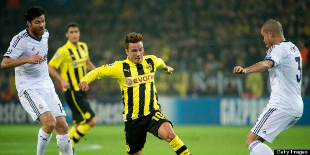 Dortmund's midfielder Mario Goetze (C) vies for the ball with Real Madrid's Portuguese defender Pepe...