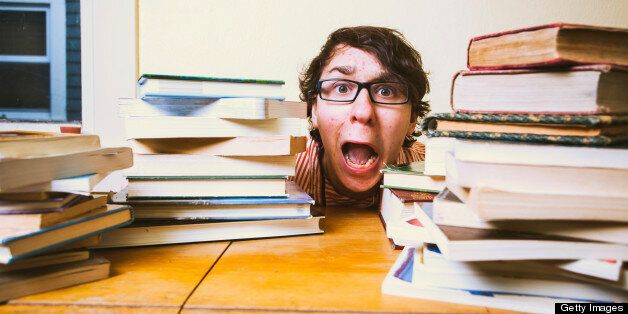 A stressed out college or high school student hiding behind piles of books on top of his desk. He is...