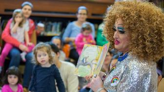 In this Saturday, May 13, 2017 photo, Lil Miss Hot Mess reads to children during the Feminist Press' presentation of Drag Queen Story Hour at the Park Slope Branch of the Brooklyn Public Library, in New York. About once a month since last fall, the Brooklyn Public Library has been presenting Drag Queen Story Hour, where performers with names such as Lil Miss Hot Mess and Ona Louise regale an audience of young children and their parents. (AP Photo/Mary Altaffer)