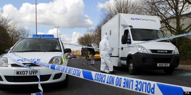 Forensic police officers examine evidence at the crime scene where two men escaped from a prison van...