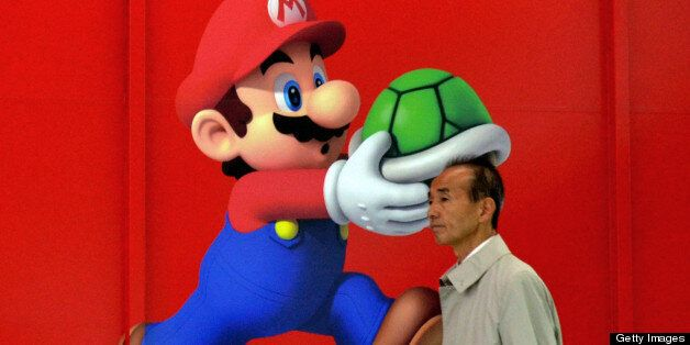 A man walks past an advertisement for Japanese videogame giant Nintendo at an electrical shop in Tokyo...
