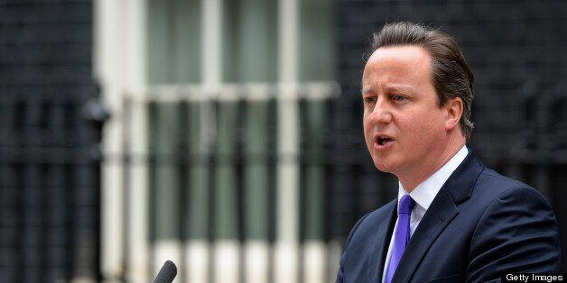 Britian's prime Minister David Cameron arrives to address media representatives at 10 Downing Street...