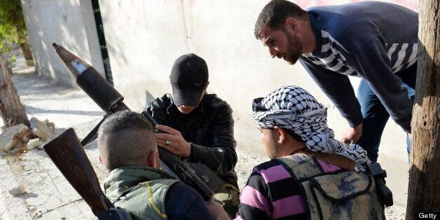 Rebel fighters prepare to launch of a rocket in the Saif al-Dawla district of the northern Syrian city...