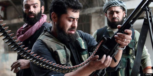 A rebel fighter loads his machine gun during fightings with regime forces on April 1, 2013 in the Sheikh...