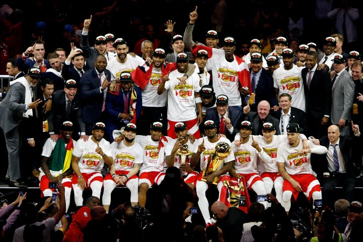Members of the Toronto Raptors organization pose for a photo with the Larry O'Brien Trophy after Game 6 of the NBA Finals at Oracle Arena in Oakland, Calif., on June 13, 2019.
