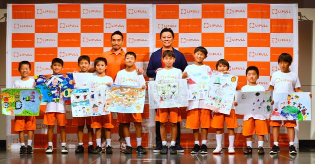 LIFULLの発表イベントに参加した井上高志社長(後列右)とサッカー日本代表の長友佑都選手(後列左)=東京・新宿