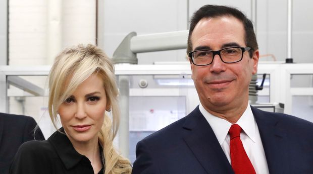 Treasury Secretary Steven Mnuchin, right, and his wife Louise Linton, hold up a sheet of new $1 bills, the first currency notes bearing his and U.S. Treasurer Jovita Carranza's signatures, Wednesday, Nov. 15, 2017, at the Bureau of Engraving and Printing in Washington. The Mnuchin-Carranza notes, which are a new series of 2017, 50-subject $1 notes, will be sent to the Federal Reserve to issue into circulation. (AP Photo/Jacquelyn Martin)