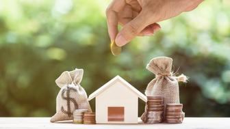 Saving money, home loan, mortgage, a property investment for future concept. A man hand putting money coin over small residence house and money bag with nature background. A sustainable investment.