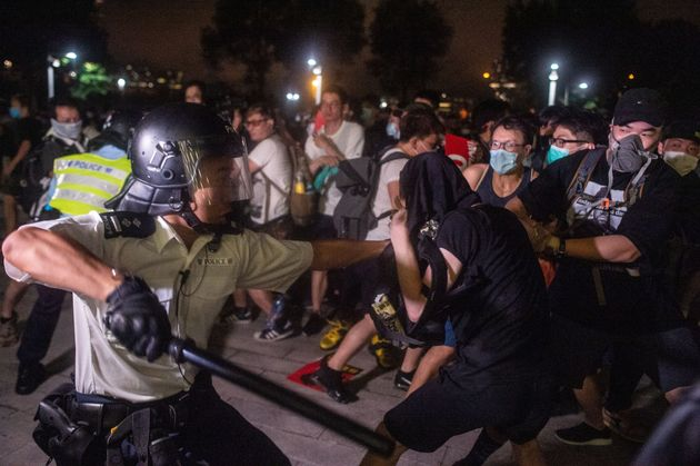 A police officer swings his baton as he restrains a protester during the clear up after the clash outside...
