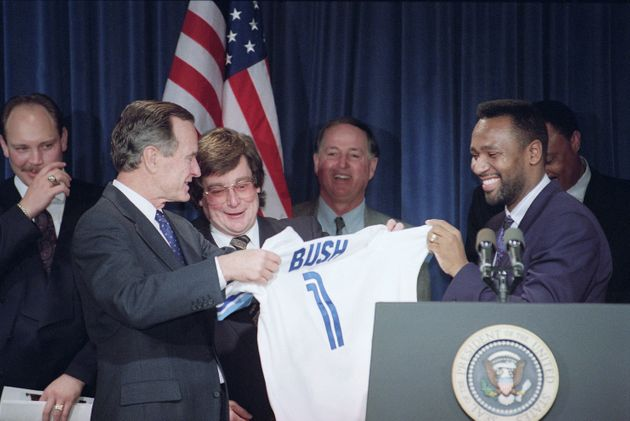 George H. W. Bush, left, accepts a Toronto Blue Jays Jersey from Jays Joe Carter, right, during a ceremony...