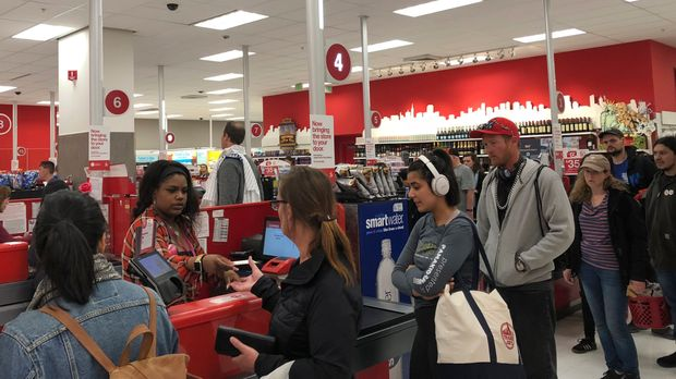 Customers wait on a long check out line at a Target store in San Francisco on Saturday, June 15, 2019.  Target suffered a technological glitch that stalled checkout lines at its stores worldwide Saturday, exasperating shoppers and eating into sales at a prime time for retailers. The outage periodically prevented Target's cashiers from scanning merchandise or processing transactions. Self-checkout registers also weren't working at times, causing massive lines in some stores. (AP Photo/Michael Liedtke)