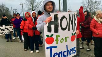 Striking teachers wave at passing cars outside Poca High School Tuesday, Feb. 19, 2019, in Poca, W.Va.  Poca is in Putnam County, the only county in the state where public schools were held on the first day of the strike. (AP Photo/John Raby)