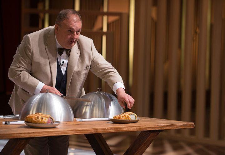 O chef ErickJacquin mostra exemplos de Bife Wellington para os participantes da prova final da repescagem.