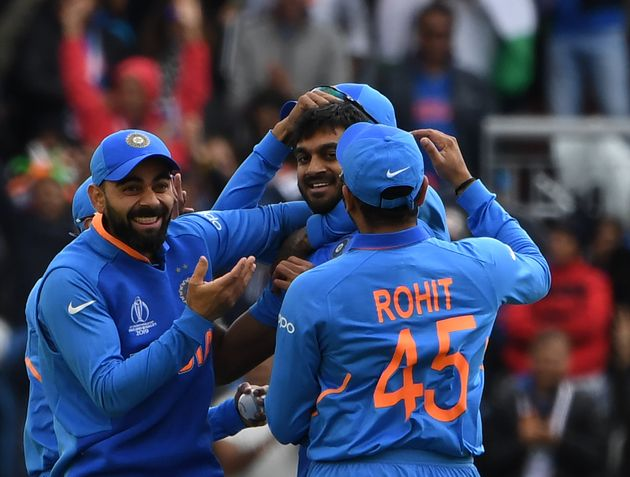 Vijay Shankar (C) celebrates with Virat Kohli (L) and teammates after the dismissal of Pakistan's
