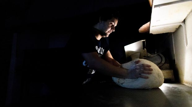 A pizza maker uses battery powered lamps to illuminate his work space during a blackout inside the delivery-only pizza shop in Buenos Aires, Argentina, Sunday, June 16, 2019. A widespread power failure early Sunday morning left a large section of South America, including all of Argentina and Uruguay, without power. AP Photo/Tomas F. Cuesta)