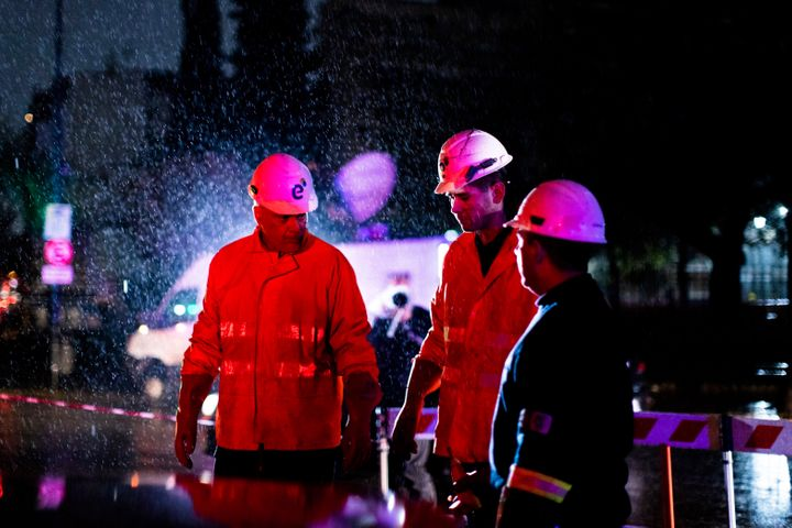 Technicians of Edenor electricity company stand under the rain as they work to fix a generator during a blackout in Buenos Ai