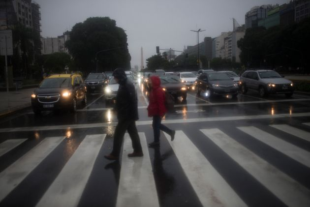 Pedestrians walk in front the Obelisk, during the blackout and under a heavy rain, in Buenos Aires, Argentina,...