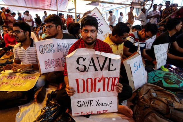 A doctor holds a placard at a government hospital during a strike demanding