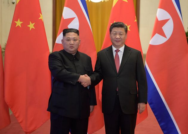 North Korean leader Kim Jong Un, left, and Chinese President Xi Jinping shake hands as they pose for...