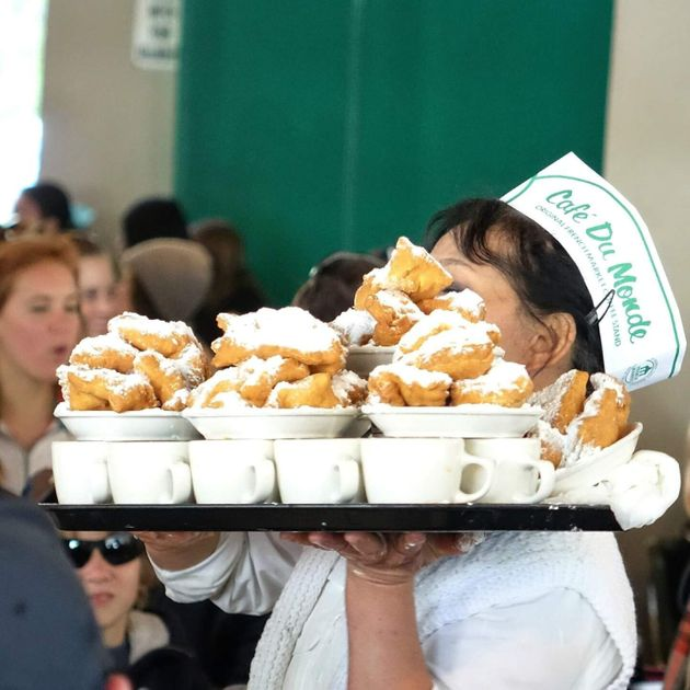 A server at New Orleans' legendary Cafe Du Monde carries a tray of coffee and fresh